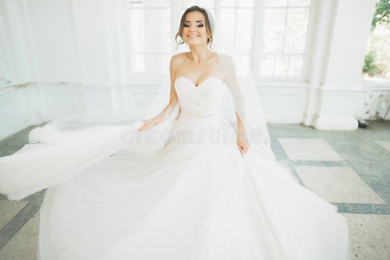 Piękna panna młoda w ślubnej sukni z długą pełną spódnicą, białym tłem, tanem i uśmiechem, obrazy royalty free