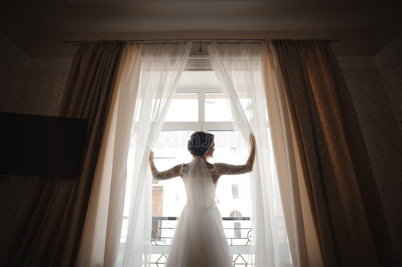 Piękna panna młoda w białej ślubnej sukni otwiera zasłony zdjęcie royalty free