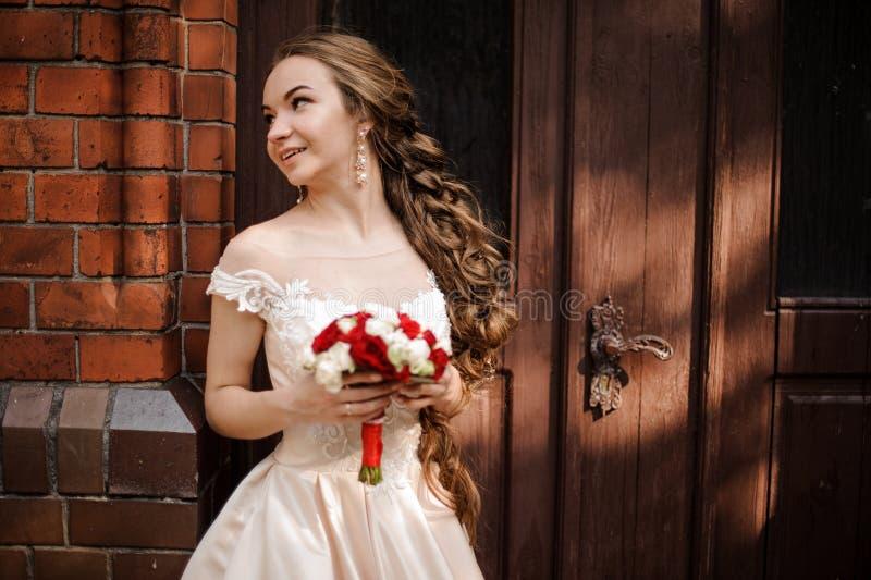 Piękna panna młoda w białej ślubnej sukni z ślubną bukiet pozycją blisko drewnianego drzwi fotografia stock