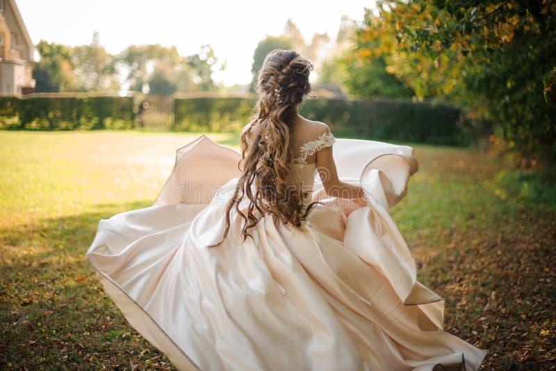 Piękna panna młoda w białym ślubnej sukni bieg w parku obraz stock