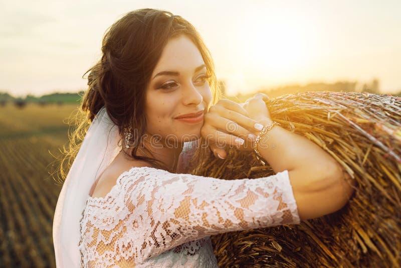 Piękna panna młoda w koronkowej sukni jest uśmiechnięta na tle natura zdjęcie royalty free
