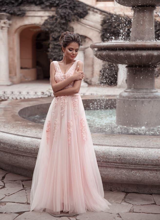 Piękna panna młoda w różowej ślubnej sukni Plenerowy romantyczny portret atrakcyjna brunetki kobieta z fryzurą w bal sukni z fotografia royalty free