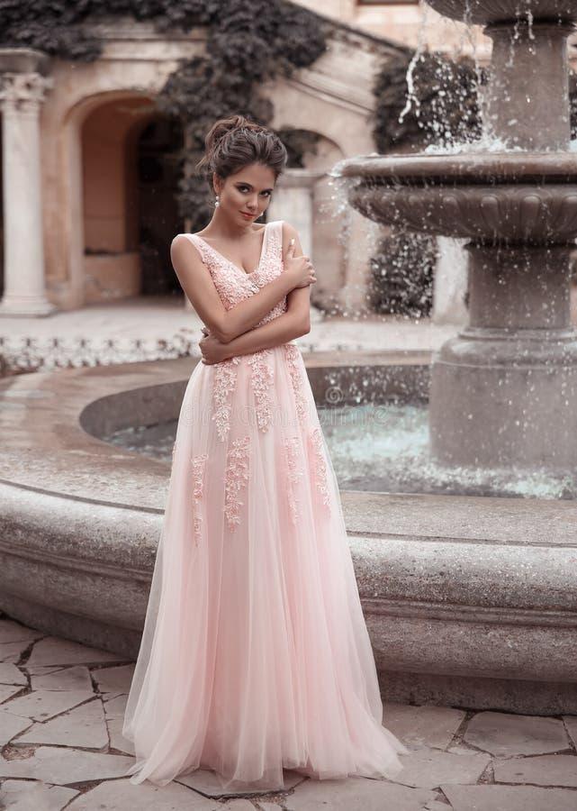 Piękna panna młoda w różowej ślubnej sukni Plenerowy romantyczny portret atrakcyjna brunetki kobieta z fryzurą w bal sukni z obraz stock
