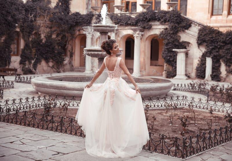 Piękna panna młoda w różowej ślubnej sukni Plenerowy romantyczny portret atrakcyjna brunetki kobieta z fryzurą w bal sukni z zdjęcia stock