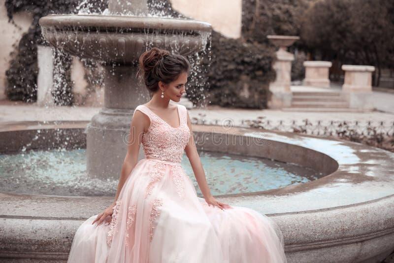 Piękna panna młoda w różowej ślubnej sukni Plenerowy romantyczny portret atrakcyjna brunetki kobieta z fryzurą w bal sukni z obraz royalty free