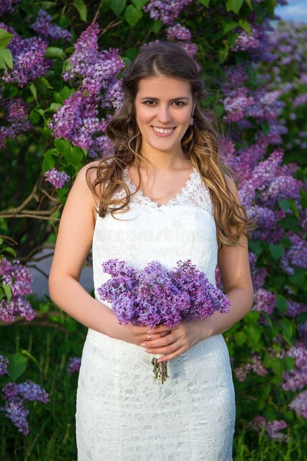Piękna panny młodej pozycja z kwiatami zbliża kwitnącego lilego drzewa fotografia stock