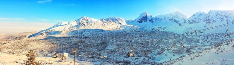 Piękna panorama nakrywający pasmo górskie słońce błyszczy w ranku, wewnątrz stać na czele narciarskich dźwignięcia fotografia royalty free