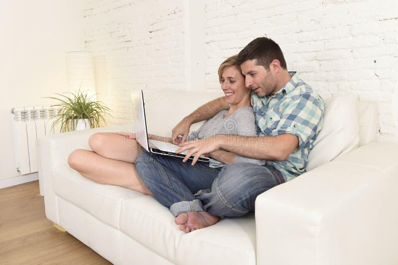 Piękna para w miłości na leżance wraz z laptopu szczęśliwym używa internetem w domu zdjęcie royalty free