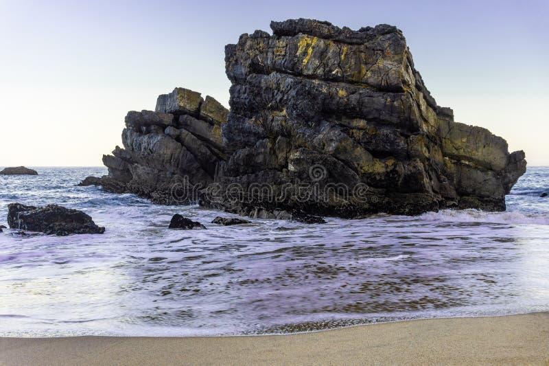 Piękna piaskowata plaża z skałami na Atlantyk wybrzeżu i falach ocean obraz royalty free