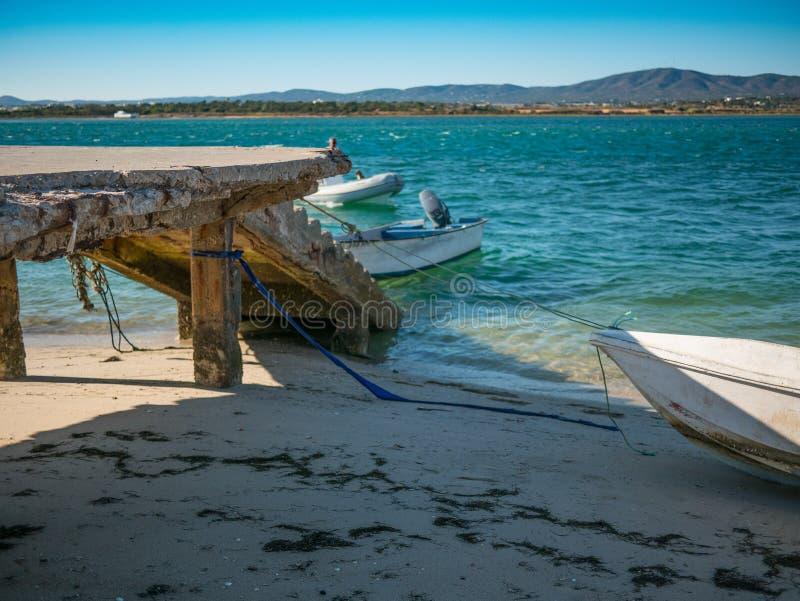 Piękna plaża z kamiennym jetty i łodziami w Algarve, Portugalia obraz royalty free
