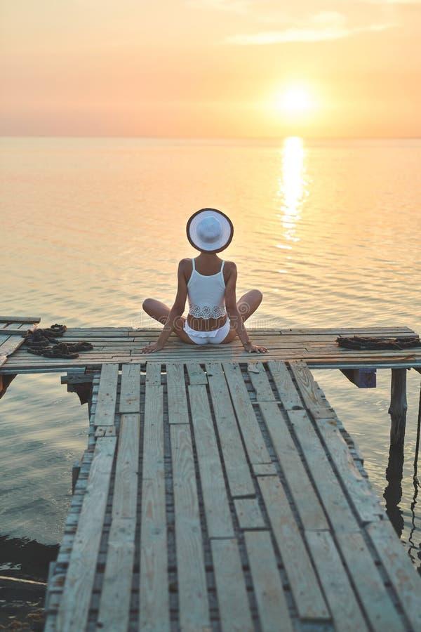 Piękna plciowa kobieta w białym bikini na drewnianym molu przeciw i kapeluszu zmierzchowi i morzu obraz royalty free