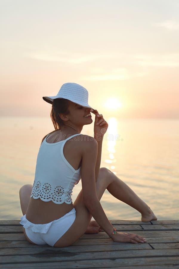 Piękna plciowa kobieta w białym bikini na drewnianym molu przeciw i kapeluszu zmierzchowi i morzu zdjęcia royalty free