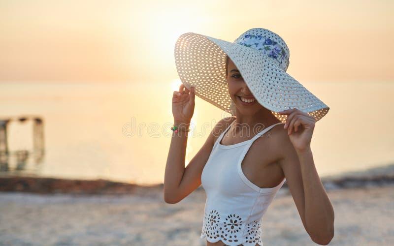 Piękna plciowa kobieta w białym bikini przeciw i kapeluszu zmierzchowi i morzu obrazy stock
