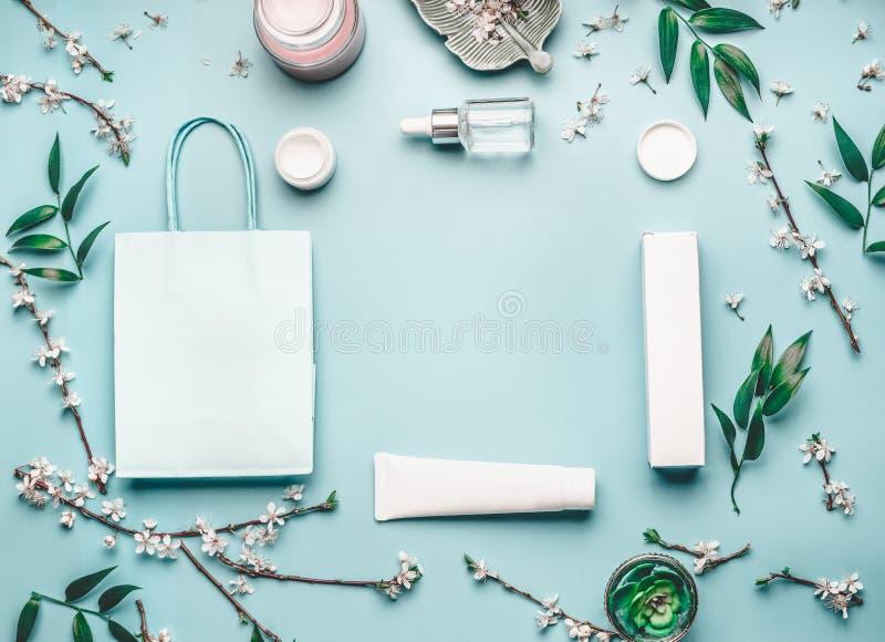 Piękna pojęcie z twarzowymi kosmetycznymi produktami, torba na zakupy i czereśniowym okwitnięciem na pastelowym błękitnym desktop fotografia royalty free