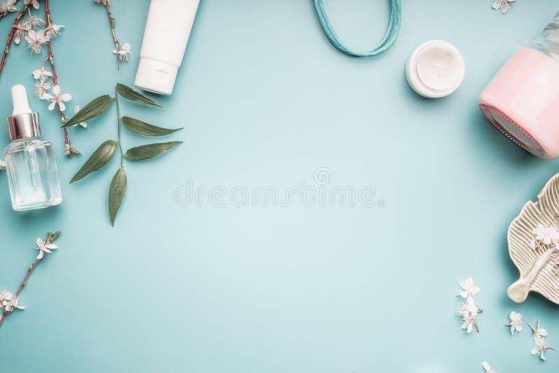 Piękna pojęcie z twarzowymi kosmetycznymi produktami, zieleń liśćmi i czereśniowym okwitnięciem na pastelowym błękitnym desktop, fotografia stock