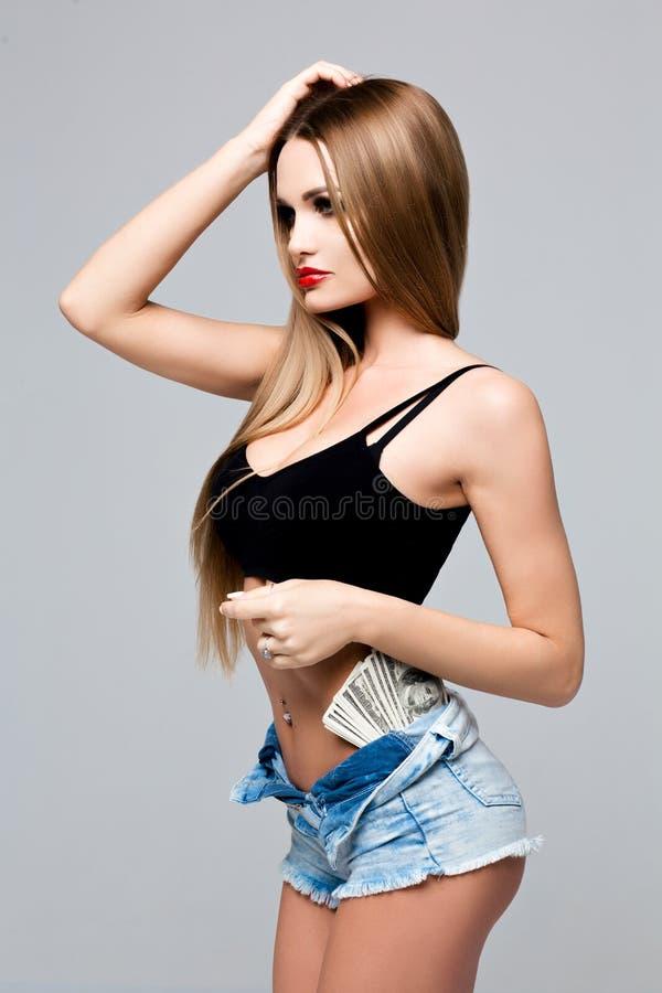 Piękna postać w drelichowym stroju z pieniądze w skrótach 100 dolarowych rachunków w ubraniach dziewczyna Nikły piękny zdjęcia royalty free