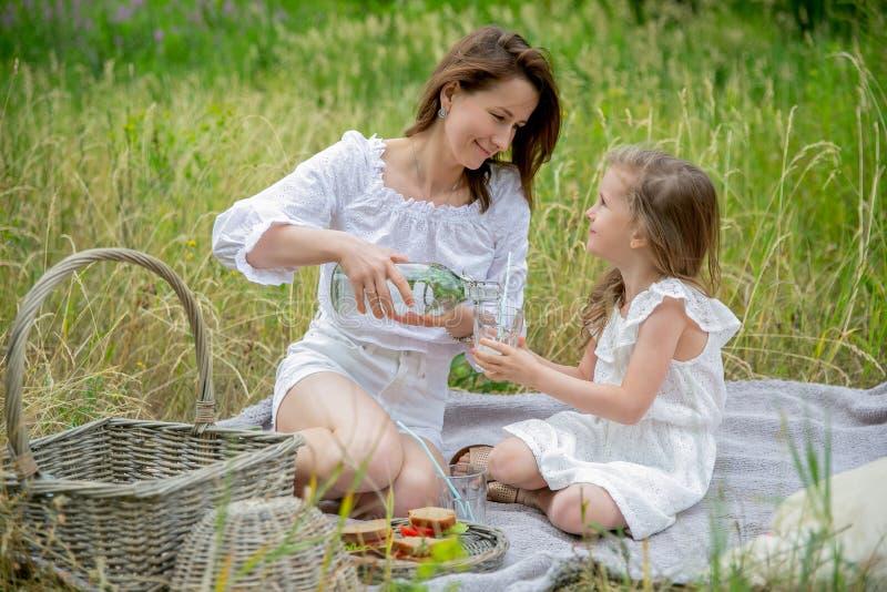 Piękna potomstwo matka i jej mała córka w bielu ubieramy mieć zabawę w pinkinie Siedzą na szkockiej kracie i mama nalewa zdjęcia royalty free
