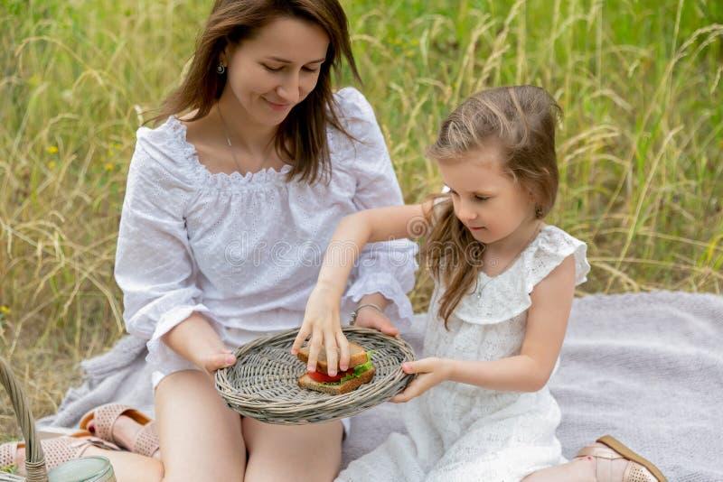 Piękna potomstwo matka i jej mała córka w bielu ubieramy mieć zabawę w pinkinie Siedzą na szkockiej kracie na trawie, obraz royalty free