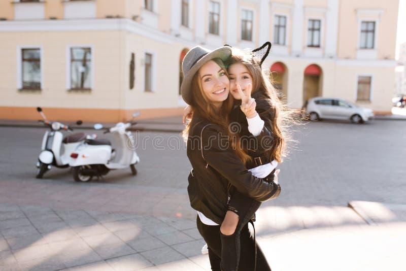 Piękna potomstwo matka w modnej skórze odziewa delikatnie trzymać jej córki która pokazywać pokoju znaka, Portret zdjęcia royalty free