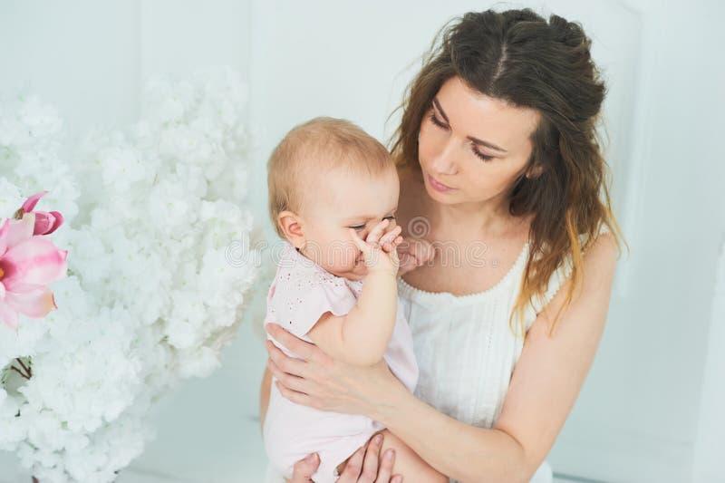 piękna potomstwo matka z dziewczynką w ona ręki Pojęcie szczęśliwa rodzina, macierzyństwo macierzysty bawić się z jej dzieckiem w fotografia stock