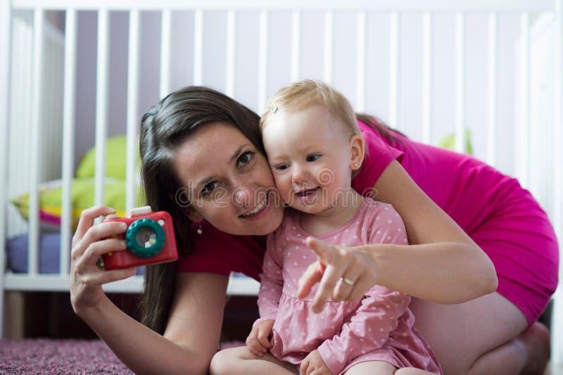 Piękna potomstwo matka z jej śliczny dziecko córki pozować zdjęcia royalty free