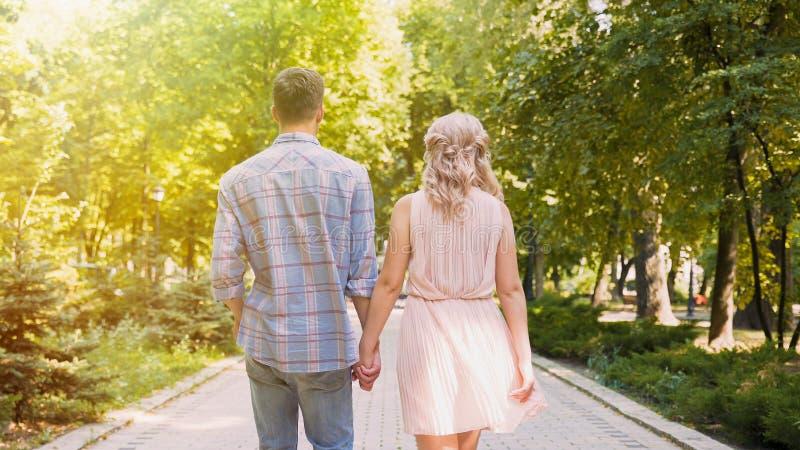 Piękna potomstwo para spaceruje przez nasłoneczniony jaskrawego - zielony park, romantyczna data zdjęcie royalty free