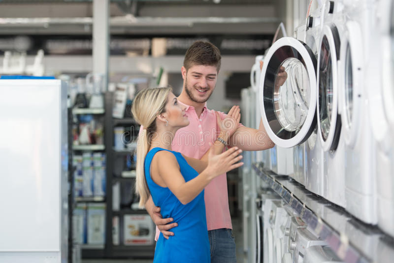 Piękna potomstwo pary zakupy pralka W supermarkecie obrazy royalty free