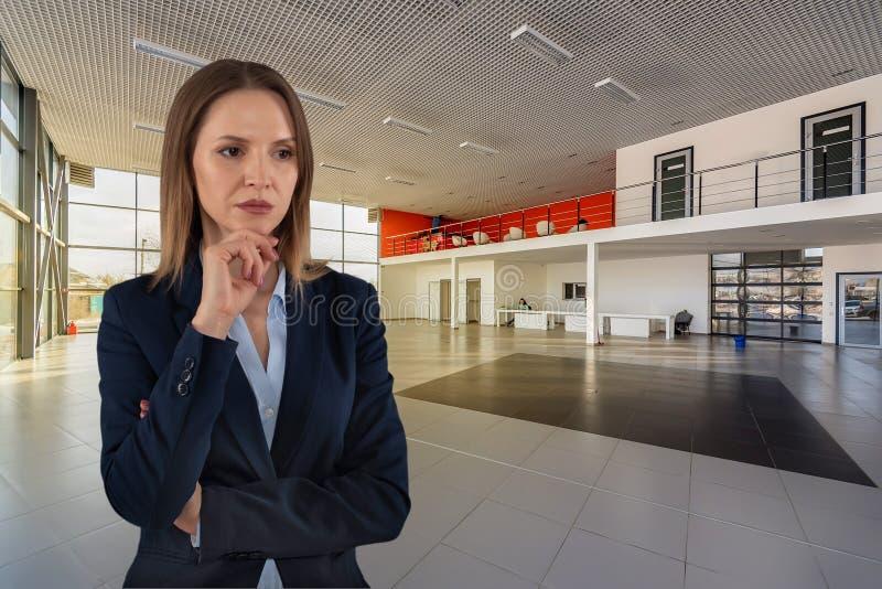 Piękna poważna biznesowa kobieta w ciemnym apartamencie na pustym handlowa centrum tle zdjęcie stock