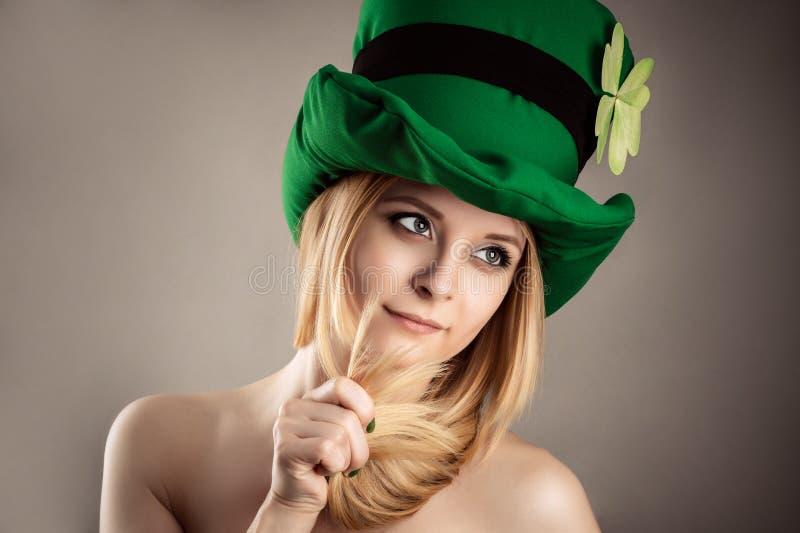 Piękna powabna blond dziewczyna w leprechaun wizerunku odizolowywającym na szarym tle fotografia royalty free