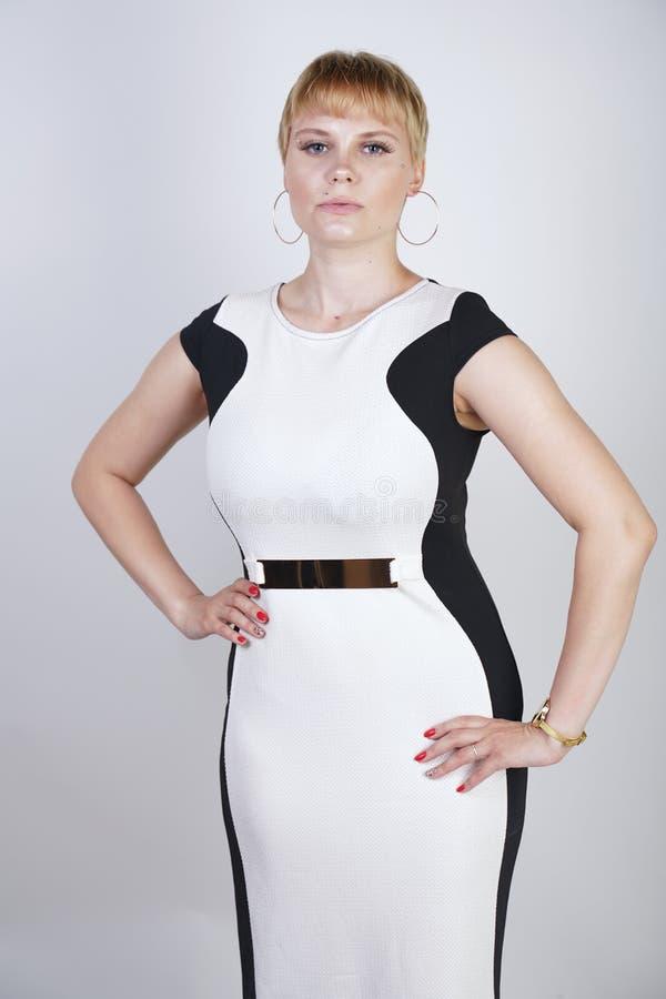 Piękna, powiększona blondynka z krótkimi włosami w modnej sukience biurowej na białym tle w Studio stylowy młody w obrazy royalty free