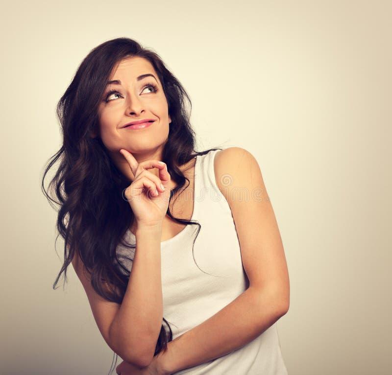 Piękna pozytywna młoda przypadkowa kobieta z palcem pod twarzą zdjęcie royalty free