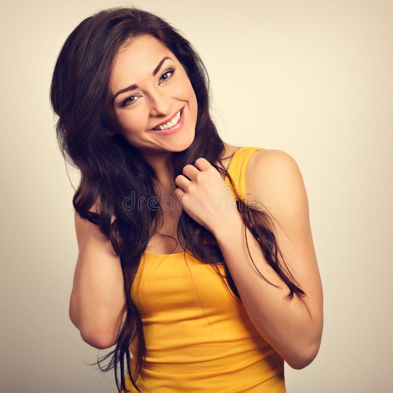 Piękna pozytywna szczęśliwa roześmiana kobieta w żółtej koszula z zbyt zdjęcia royalty free