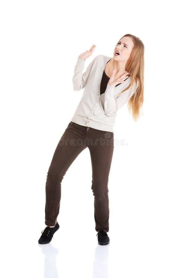 Piękna przypadkowa kobieta kuca od sth ciężkiego nad ona. obraz stock