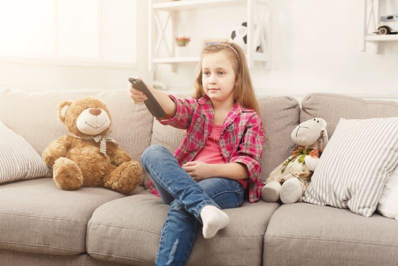 Piękna przypadkowa mała dziewczynka ogląda tv podczas gdy siedzący na kanapie w domu zdjęcie royalty free