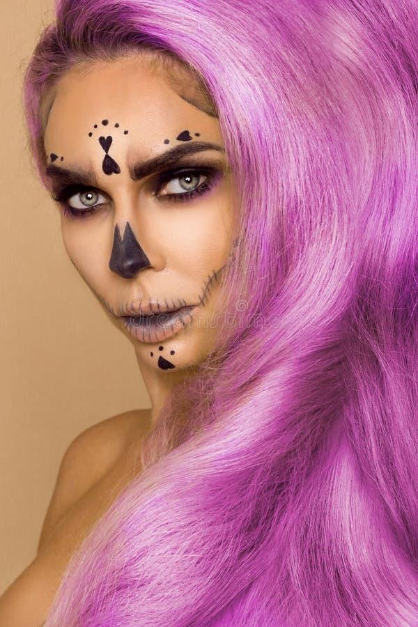Piękna różowa kobieta w Halloweenowym makeup w różowym włosy na beżowym tle w studiu i Makeup artysty kościec, potwór, obraz stock