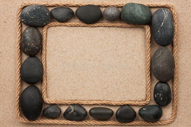 Piękna rama z arkany i czerni kamieniami na piasku obraz royalty free