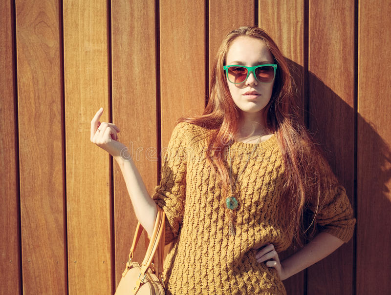 Piękna redheaded dziewczyna stoi blisko drewnianej ściany z modną dużą torbą w okularach przeciwsłonecznych fotografia royalty free