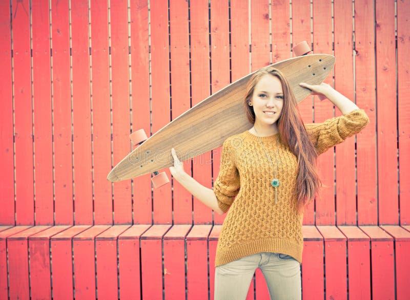 Piękna redheaded dziewczyna trzyma longboard stoi blisko czerwieni ściany zdjęcie royalty free
