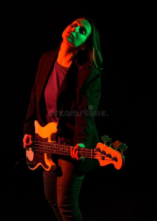 Piękna rockowa dziewczyna bawić się basową gitarę fotografia stock