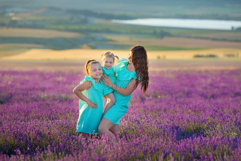 Piękna rodzina śliczne dziewczyny cieszy się życie z dziewczyny władzą na zmierzch łące lawenda Chodząca mama i córki w polu obraz royalty free