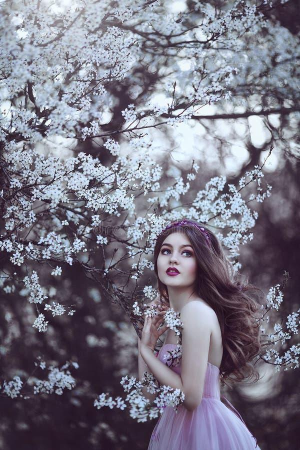 Piękna Romantyczna dziewczyna z długie włosy w menchii sukni blisko kwiatonośnego drzewa obrazy stock
