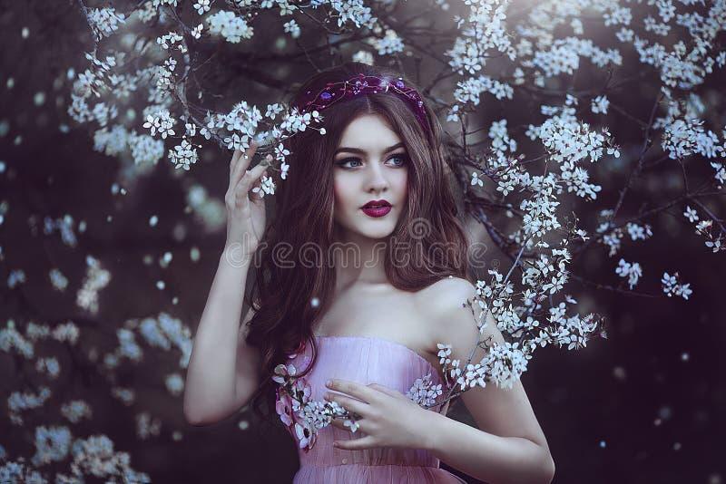 Piękna Romantyczna dziewczyna z długie włosy w menchii sukni blisko kwiatonośnego drzewa fotografia stock