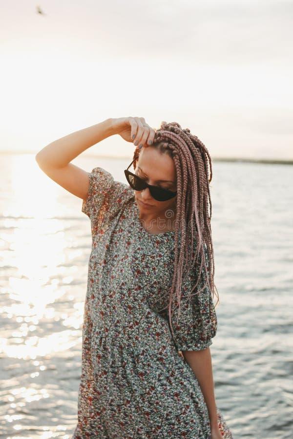 Piękna romantyczna młoda kobieta z afrykanów warkoczami w sukni na plaży, wakacje czas obraz stock