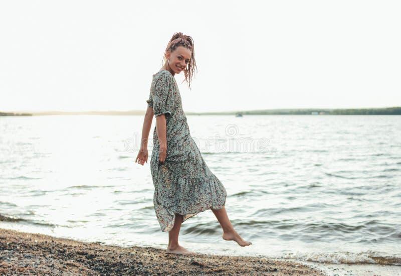 Piękna romantyczna młoda kobieta z afrykanów warkoczami w sukni na plaży, wakacje czas obrazy royalty free