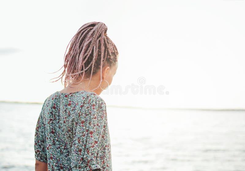 Piękna romantyczna młoda kobieta z afrykanów warkoczami w sukni na plaży, widok od za, wakacje czas zdjęcia stock