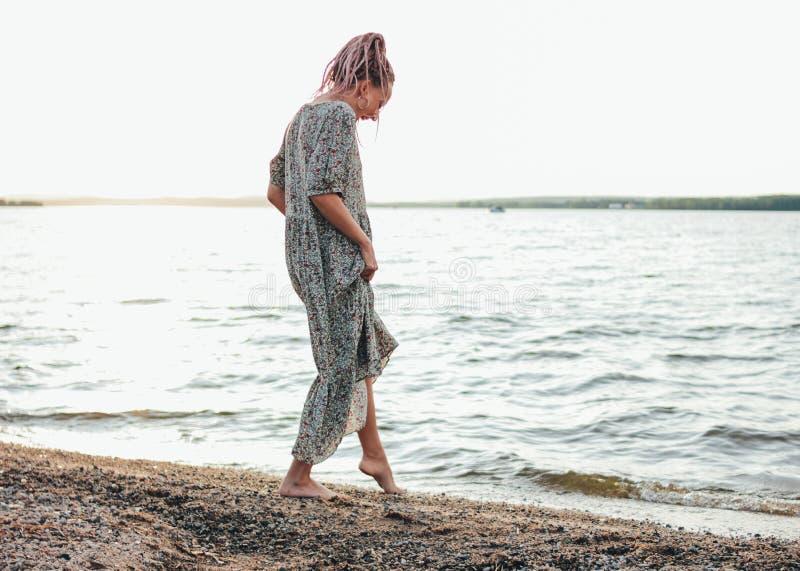Piękna romantyczna młoda kobieta z afrykanów warkoczami w sukni na plaży, widok od za, wakacje czas zdjęcie royalty free