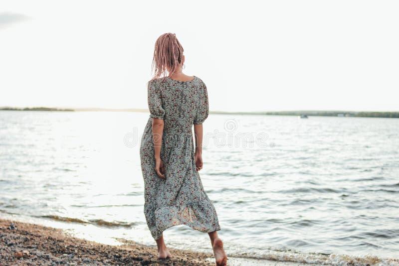Piękna romantyczna młoda kobieta z afrykanów warkoczami w sukni na plaży, widok od za, wakacje czas obrazy royalty free
