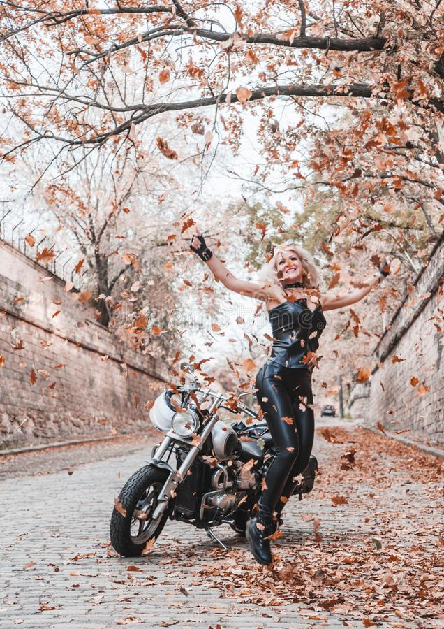 Piękna rowerzysta kobieta pozuje z motocyklem outdoors zdjęcie royalty free