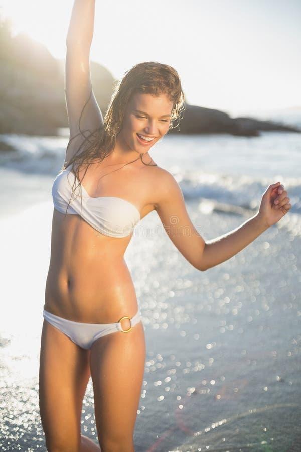 Piękna roześmiana blondynka w białym bikini przy plażą z mokrym włosy fotografia royalty free