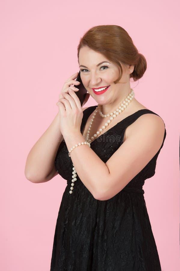 Piękna Rozochocona kobieta trzyma smartphone Kobieta w czerni sukni z perls na różowym tle zdjęcie stock